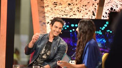 Bild på Darin som sitter i en fåtölj och blir intervjuad. Han skrattar och gör en gest med handen.