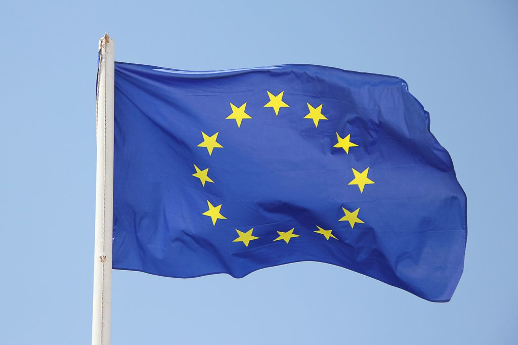 En EU-flagga är fäst på en flaggstång och vajar i vinden.