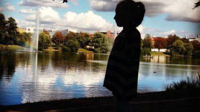 Flicka i siluett i park