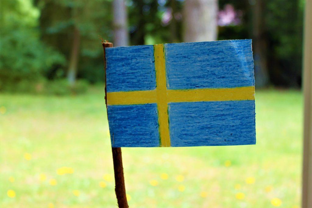 Bild på en svensk flagga som målats på ett papper med kritor.