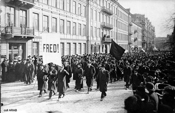 """En gammal bild från 1917. På bilden syns ett demonstrationståg. Längst fram i tåget hålls en skylt upp där det står """"Fred""""."""