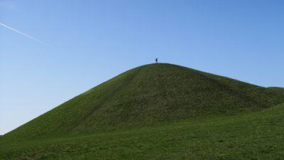 Liten människa högst uppe på grön kulle