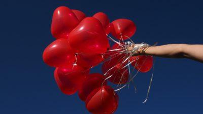Bild på en hand som håller i ett tjugotal ballonger formade som hjärtan.