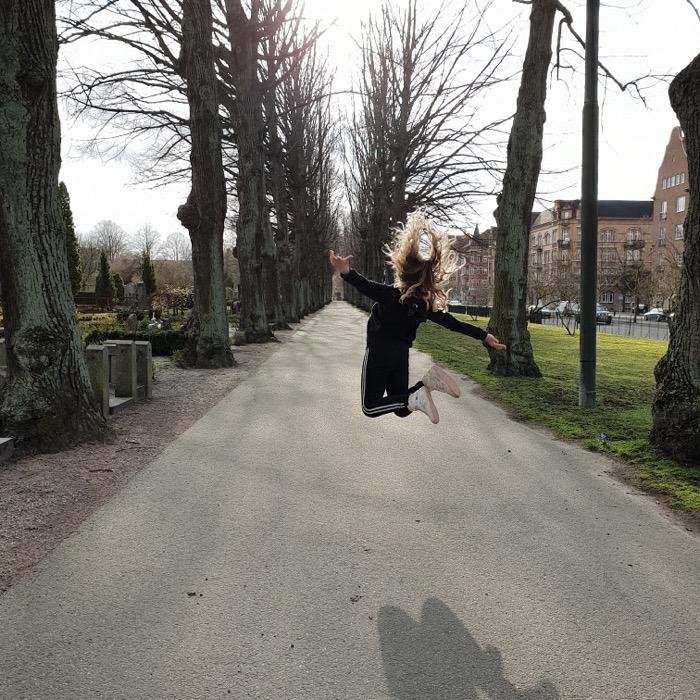 Tjej hopparpå en väg på en kyrkogård