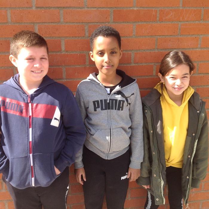 Tre elever mot en tegelvägg