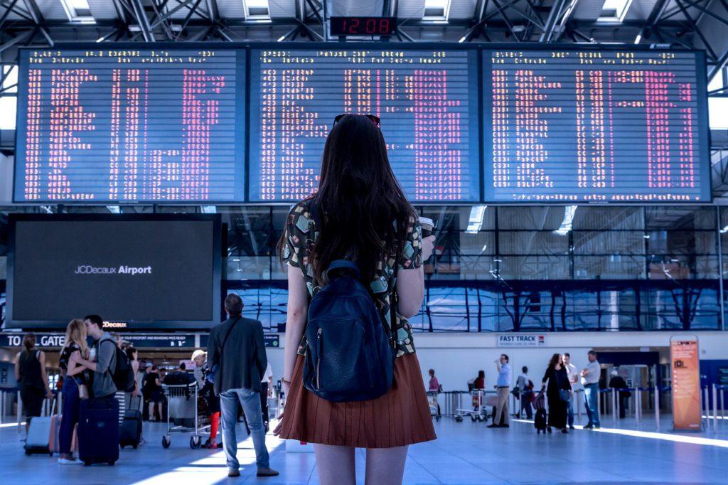 En person står framför en stor digital tavla. På tavlan visas avgångstider för flygplan.