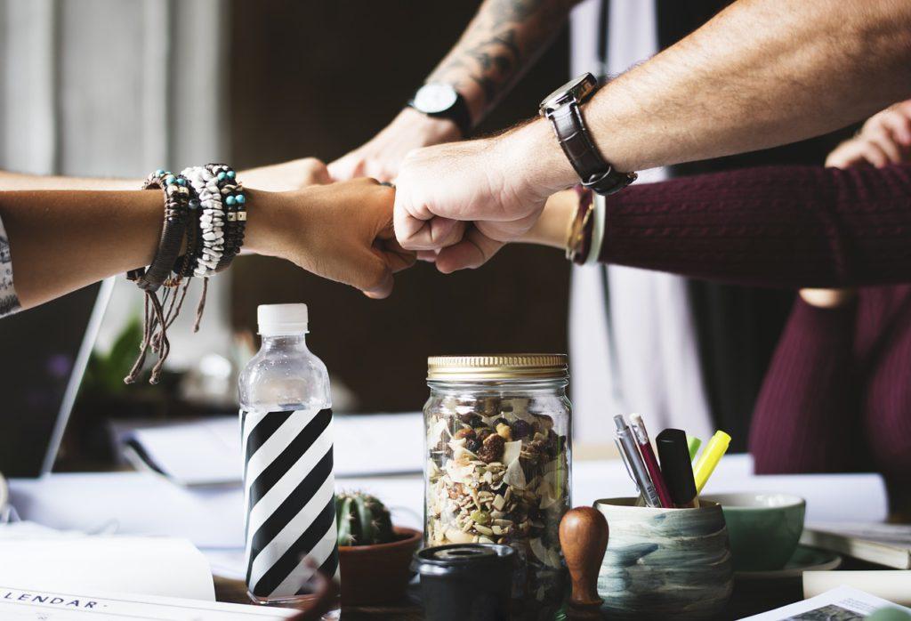 Flera människor har knutit sina händer och håller dem emot varandra så de möts i mitten.