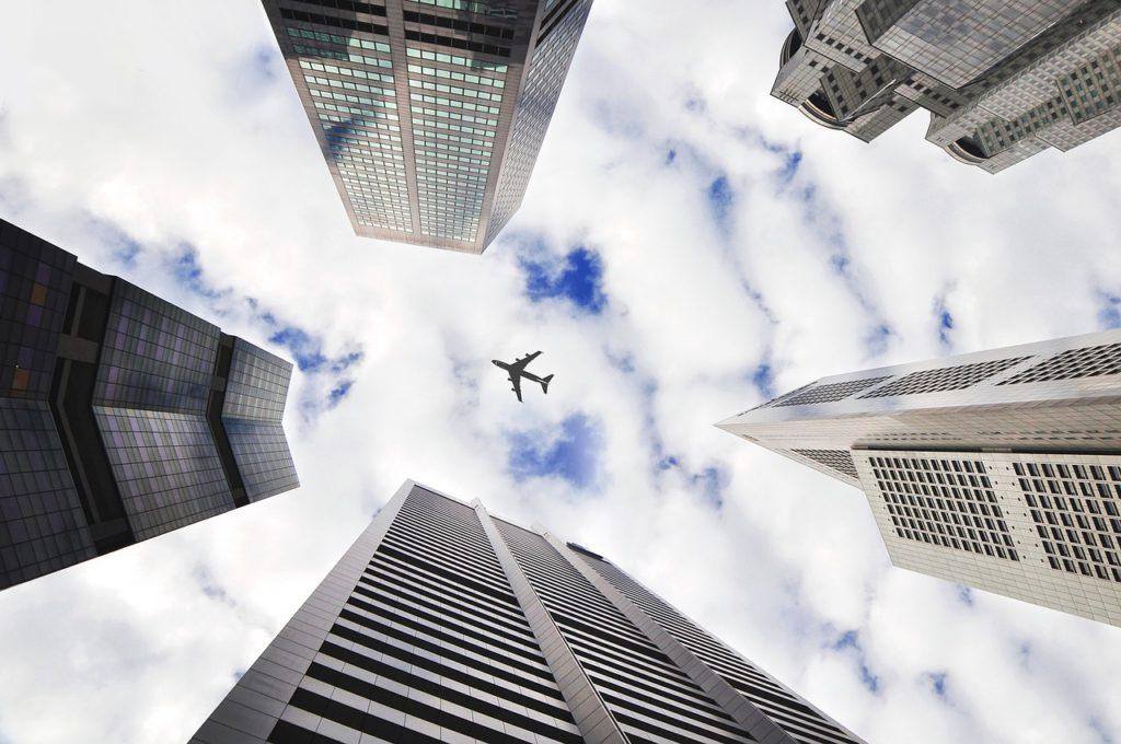 Höga skyskrapor. På himlen mellan skyskraporna flyger ett flygplan.