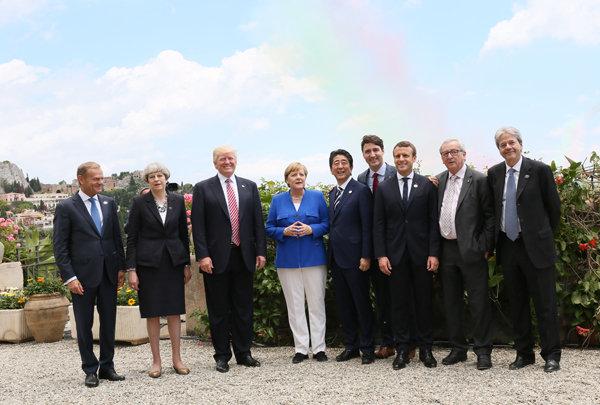 Flera av världens mest kända ledare står i en park. Några av ledarna är USA:s president Donald Trump och Frankrikes president Emmanuel Macron.