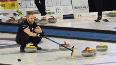 Bild på Niklas Edin under en match. Han står hukad på isen och pekar var hans medspelare ska träffa curlingstenen för att slå bort motståndarna.