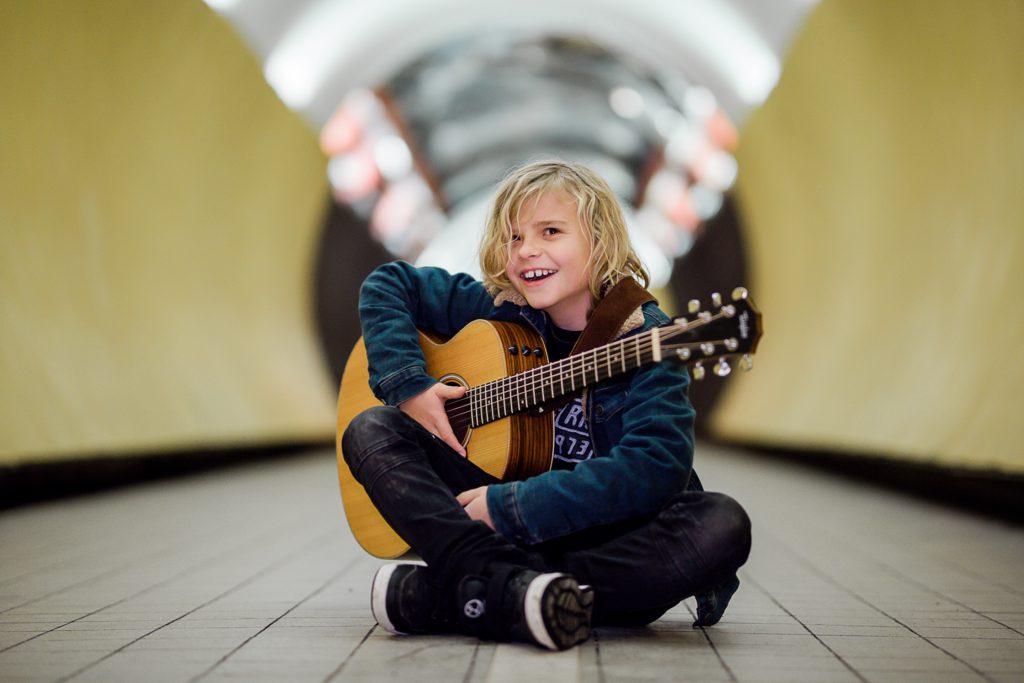 Oscar sitter med en gitarr i famnen