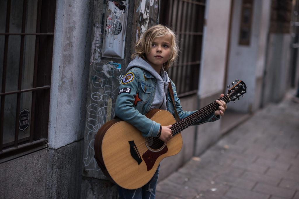 Oscar står på en gata med en gitarr i famnen