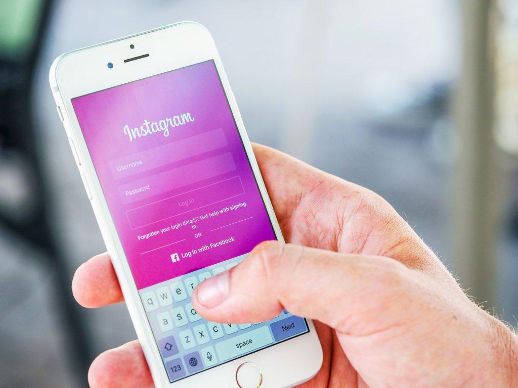 Bild på en hand som håller i en mobil. På displayen syns Instagrams förstasida.