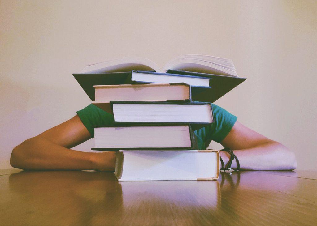 Bild på en person som gömmer sig bakom en hög av böcker.