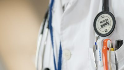 Inzoomad bild på en läkare. Runt läkarens hals hänger ett stetoskop och i bröstfickan är flera pennor fastklämda.