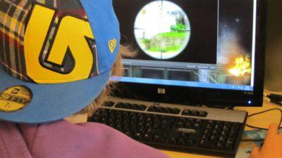 Bild på en person bakifrån som sitter och spelar datorspel.