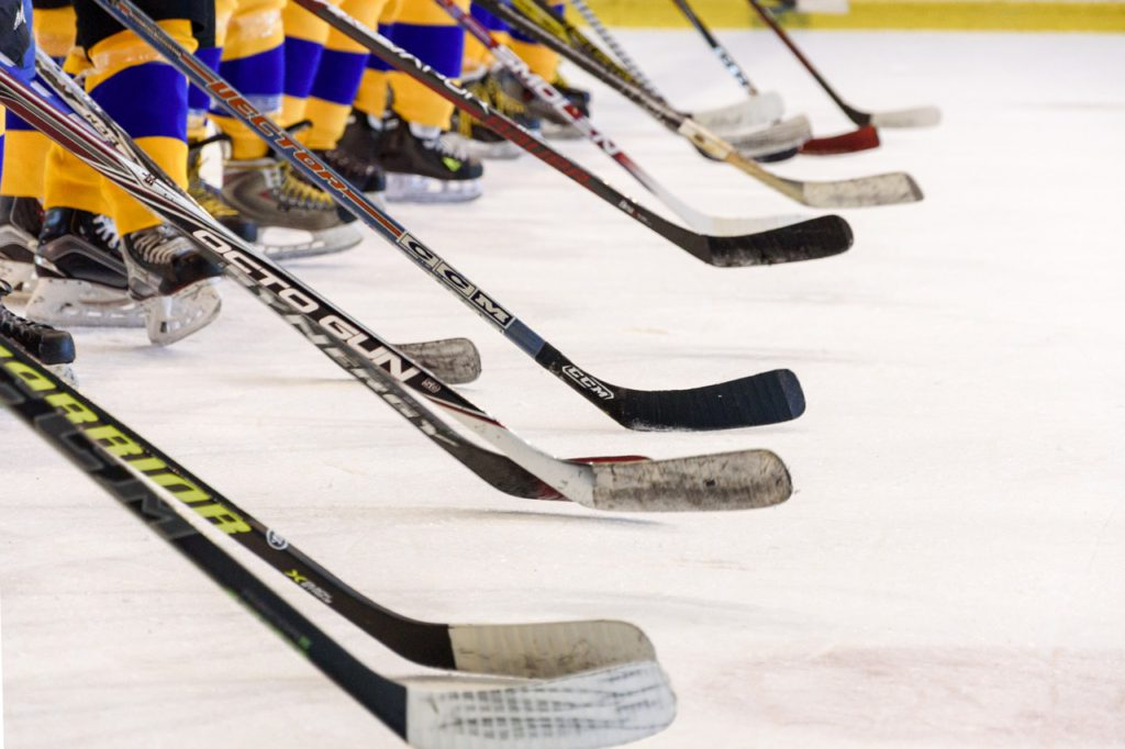 Bild på ett hockeylag som tackar motståndarna efter en match. De står med sina hockeklubbor lutade mot isen.