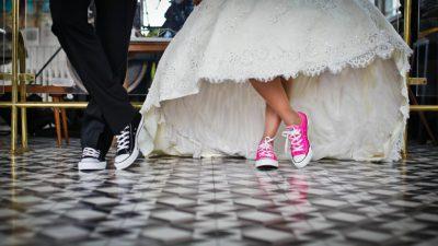 Bild på ett bröllopspars ben. Den ena personen har snygga välstrukna byxor och den andra en bröllopsklänning.