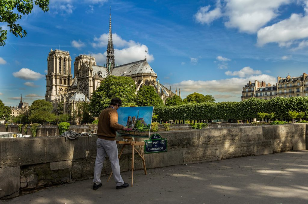 Bild på en man som står i solen och målar av Notre Dame från avstånd.