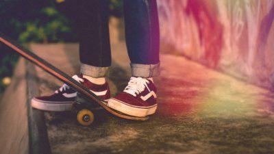Bild på en persons skejtboard och fötter. Personen ska precis åka ner för en ramp.