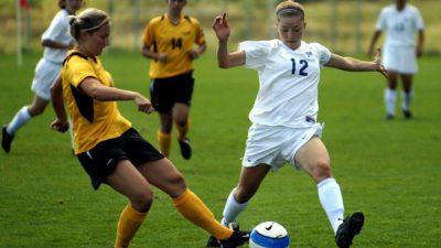 Några tjejer i fotbollskläder slåss om vem som först ska komma fram till bollen. De springer allt vad de har och stirrar fokuserat på bollen båda två.