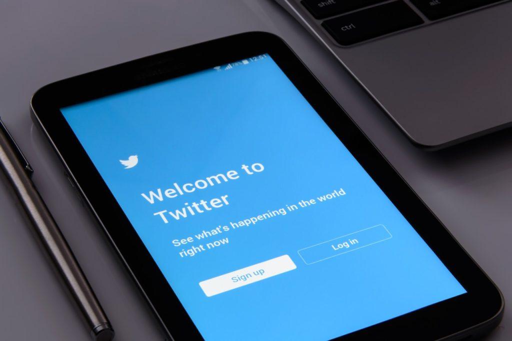 Bild på en surfplatta som ligger på ett bord. På surfplattan syns förstasidan till Twitter.