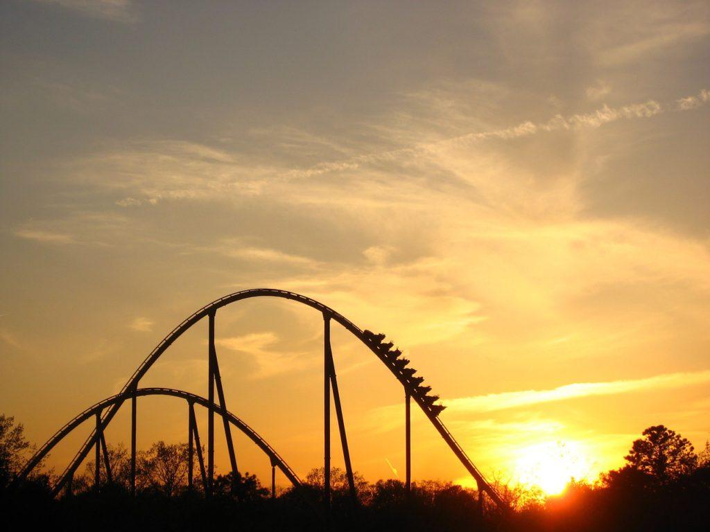 Bild på en berg- och dalbana. Bilden är tagen på avstånd och solen håller precis på att gå ner vilket gör bilden mystisk och häftig.