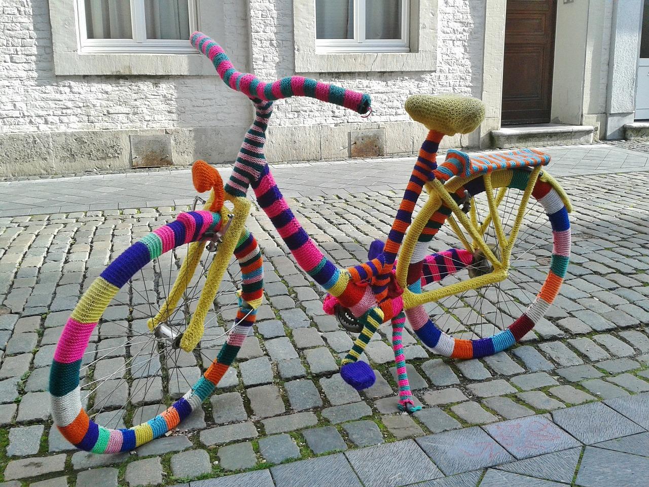 Bild på en cykel som är parkerad på en kullerstensgata. Någon har virkat kläder till cykeln, den är helt täckt i massa olika färger.