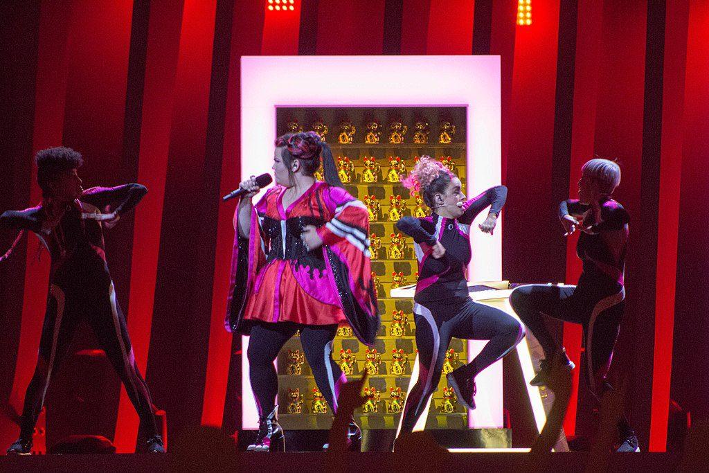 Bild från Eurovision 2018. På scenen syns artisten Netta med fyra dansare i bakgrunden. Hon håller i en mick och dansarna gör stora gester.