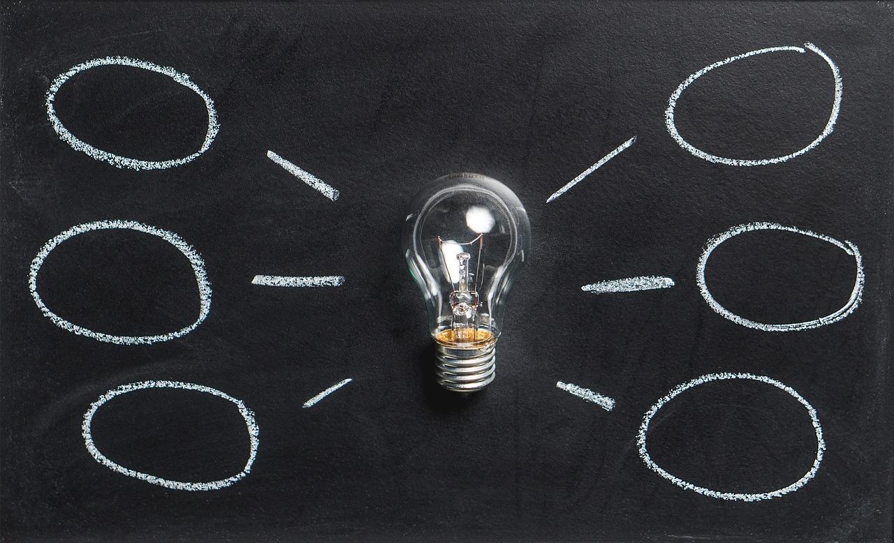 Bild på en glödlampa som ligger på en griffeltavla. På griffeltavlan har någon ritat streck och tankebubblor från glödlampan.