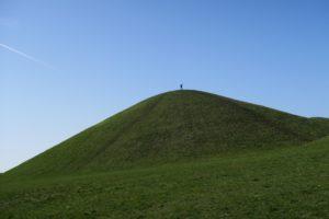 Grön kulle med pojke uppe på toppen