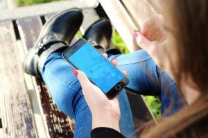 Bild på tjej med mobil i handen