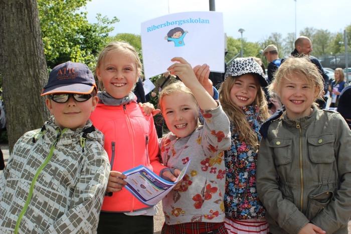 Fem glada elever utanför en fotbollsarena