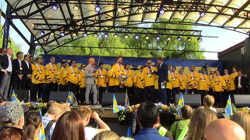 Det svenska VM-laget står i sina hockeytröjor uppe på en stor scen i Kungsträdgården i Stockholm. I bakgrunden syns träd och framför scenen står människor med svenska flaggor.