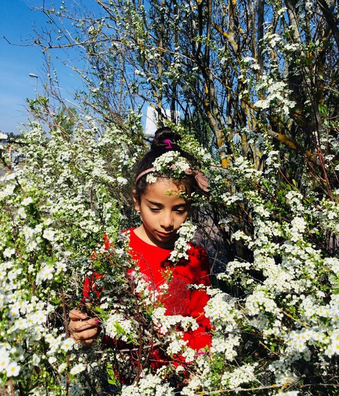 Flicka mitt i blommande buske