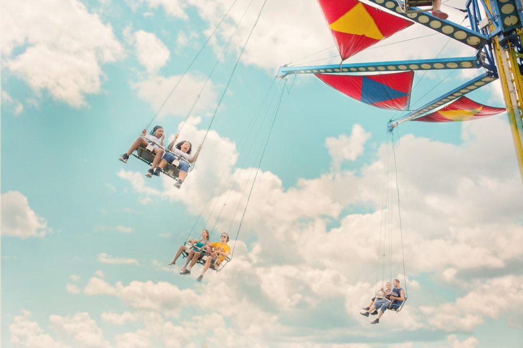 Bild på barn som åker en karusell som ger fjärilar i magen. Karusellen snurrar runt och har gungor där de som åker kan sitta två och två.