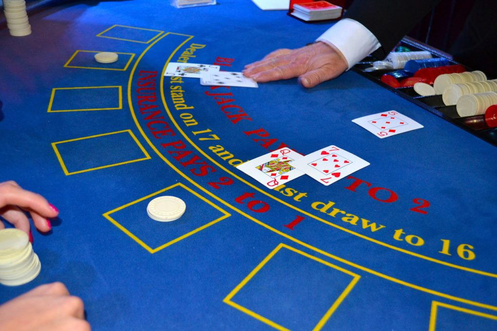 Bilden visar ett bord på ett casino. Två personer har satsat pengar och visat sina kort.