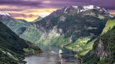 Bild på en fantastik utsikt över en fjord i Norge. Det är solnedgång bakom bergen och i vattnet ligger två stora båtar.