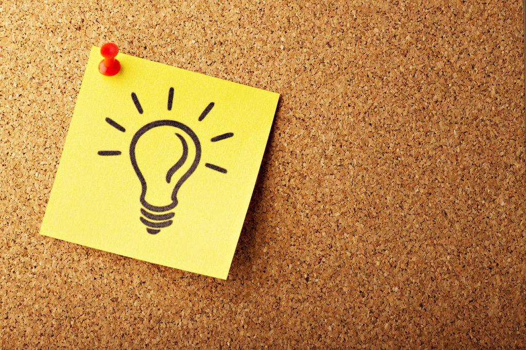 Bild på en post-it-lapp med en glödlampa som nålats upp på en tavla.