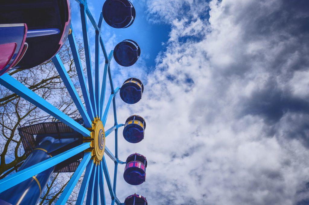 Bild på ett pariserhjul underifrån. Molnen på himlen håller på att spricka upp.