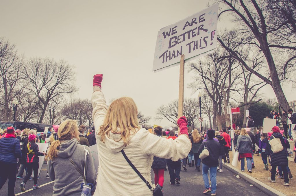 Bilden visar en manifestation för kvinnor. På bilden syns en person som håller i en skylt och knyter näven i luften. Runt om henne går personer iklädda rosa mössor. Mössorna är en symbol för tjejer och kvinnors rättigheter.