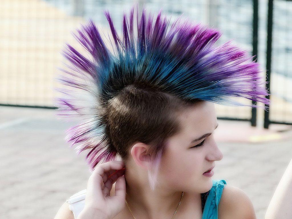 Bild på ej tjej i punkfrisyr. Hon har tuppkam i flera olika färger och rakat hår på sidorna av huvudet.