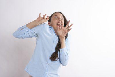 En person ser livrädd ut. Hon lutar sig bakåt och håller upp händerna för ansiktet som gör en grimas med stora ögon och mungipor som går nedåt..