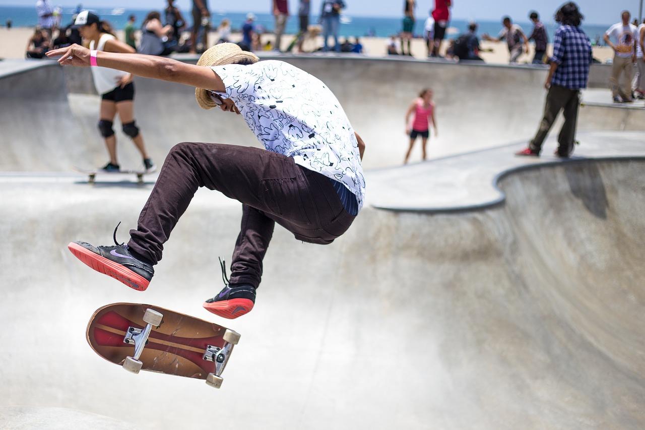 En person gör ett coolt trick på sin skejtboard. I bakgrunden syns en skejtpark i betong där flera personer åker runt.