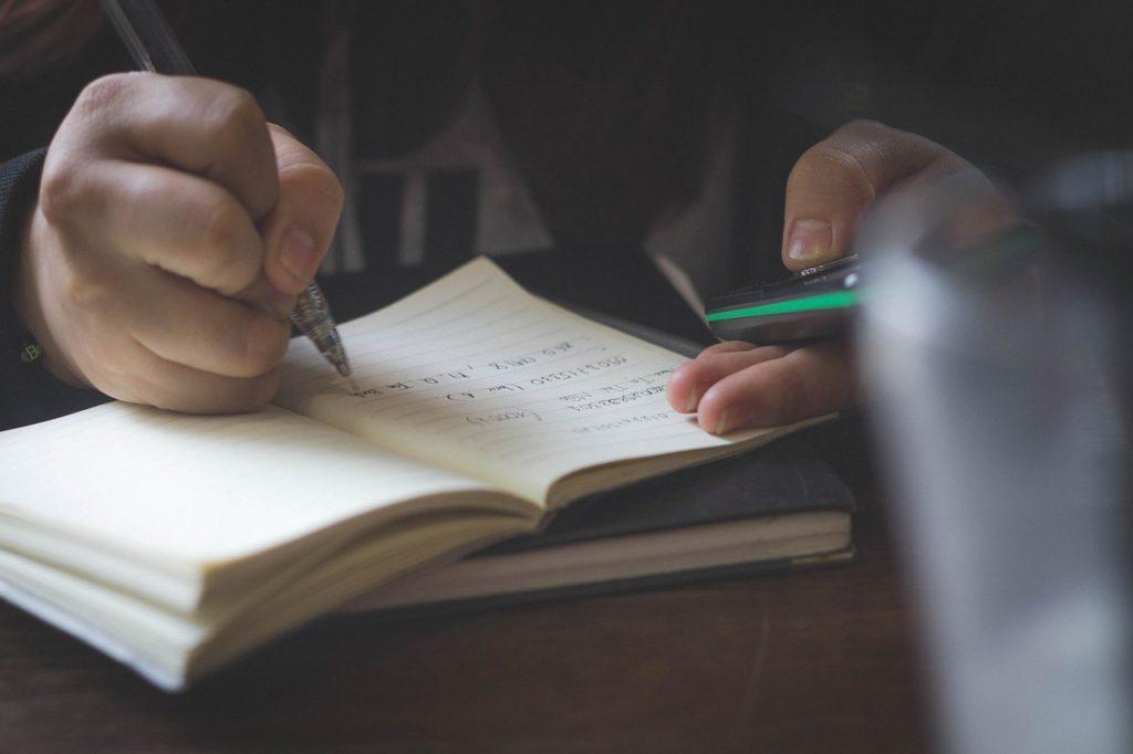 Bild på en person som sitter och skriver i ett skrivblock. I andra handen håller hen en mobiltelefon.