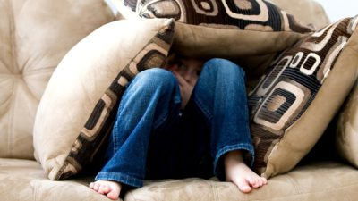 Ett barn gömmer sig under tre stora kuddar i en soffa.