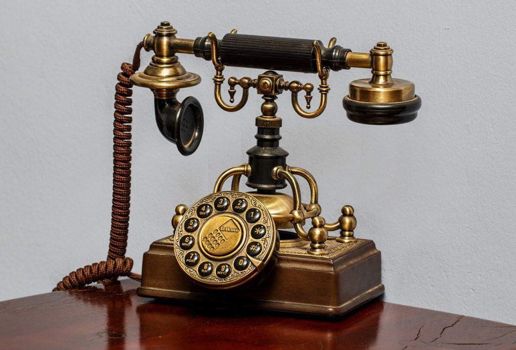En telefon i (väldigt) gammal modell står på ett bord. Den har fina detaljer och glänser i sin färg.