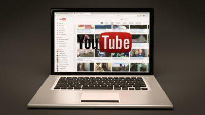 Bild på en uppfälld bärbar dator som står på ett bord. Youtubes förstasida syns.