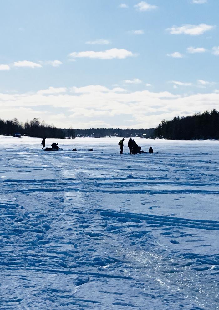 En snötäckt sjö med blå himmel ovanför. Människor syns likt siluetter långt borta.