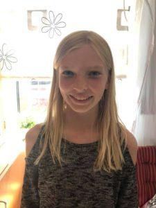 Ella har långt rakt hår och tittar in i kameran med ett stort leende.